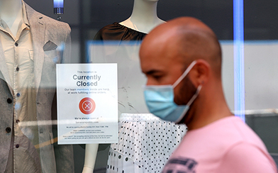 man walking past closed store wearing a face mask during coronavirus pandemic