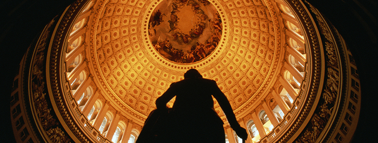 Silhouette of person standing beneath illuminated capital rotunda