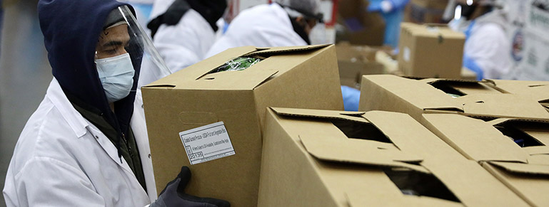 Worker packing boxes in PPE