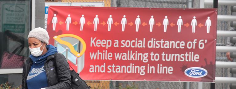 Woman walks past social distancing sign