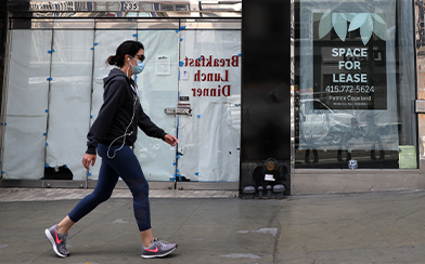 Woman wearing mask in front of vacant storefront during coronavirus pandemic