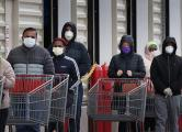 Customers wear face masks to prevent the spread of the novel coronavirus as they line up to enter a Costco Wholesale store.