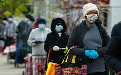 People waiting outside in masks during coronavirus pandemic